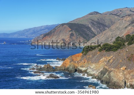 Shimmering reflective sunlight, blue skies, white clouds and waves splashing along the rugged Big Sur coastline, Big Creek Bridge viewed from a distance by Highway 1, on the California Central Coast. - stock photo