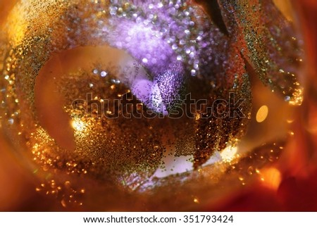 Shimmering surface of decorative christmas bulb, closeup, (red,orange and violet) - stock photo
