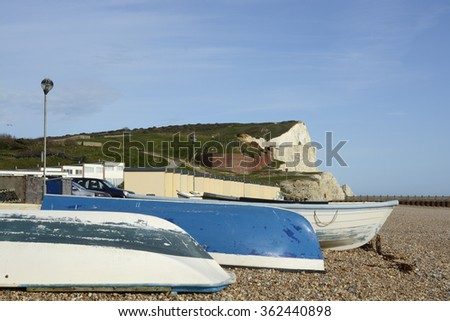 Shingle beach and chalk cliffs at Seaford in East Sussex, England. With boats on beach. - stock photo