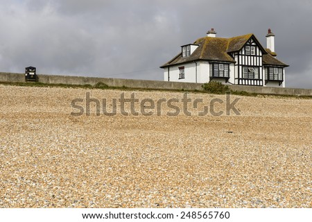 shingle beach and old cottage at New Romney, landscape of the beach with old holiday cottage near the seaside at New Romney, Kent  - stock photo