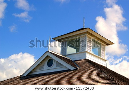 shingle rooftop against a cloudy sky - stock photo