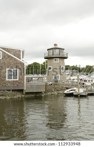 shingle style building and small lighthouse by the water in Essex Connecticut - stock photo