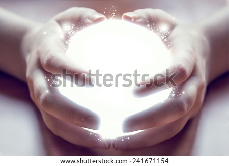 shining ball in human hands - stock photo