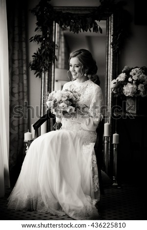 Shining bride sits in a chair behind a mirror and candles - stock photo
