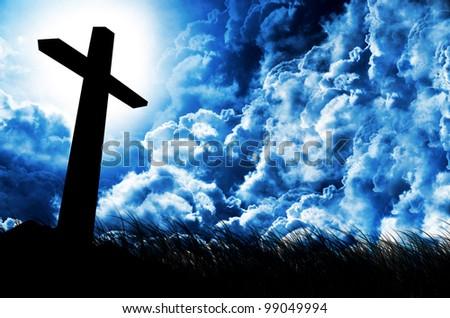 shining cross against dramatic cloudy sky - stock photo