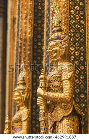 Shining golden statue of the holy man. It has bright, warm tones. A traditional crown on its head. Decorations, patterns seem very beautiful. Geometrical shapes on the decorations of buddhist statues.
