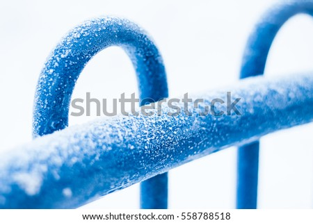 shining hoarfrost on a blue fence