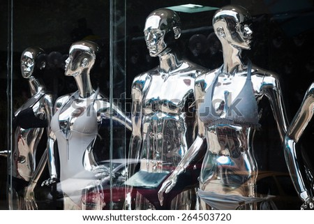 Shining metallic mannequins standing in a clothes shop window - stock photo