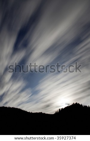 Shining moon over mountain and moving clouds - stock photo