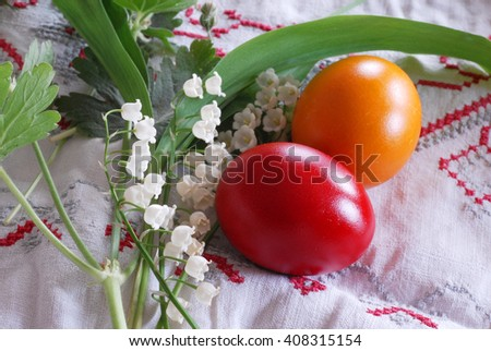 shining red and orange Easter eggs with lily of the valley plant - stock photo