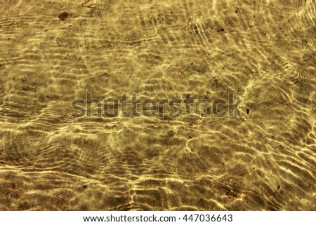 Shining sand in transparent water