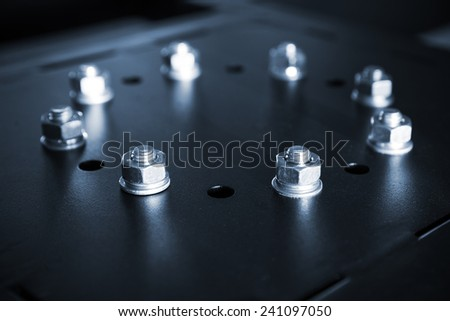 Shining steel bolts and nuts in a circle on black industrial cover - stock photo