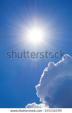 Shining sun at cloudy blue sky with lens flare, vertical shot - stock photo