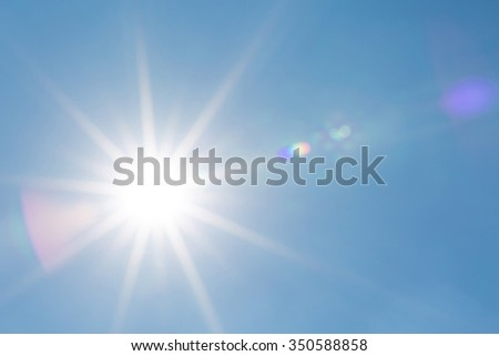 Shining Sun with flare in clear blue sky with copy space - stock photo