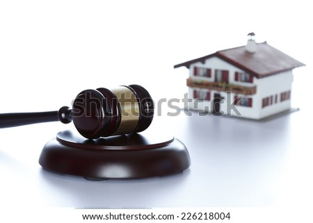 shining wooden gavel with house in background