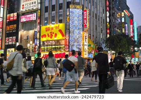SHINJUKU, TOKYO - MAY 31, 2014: Street view of Shinjuku commercial district at night, billboards with neon light and crowd of pedestrians.