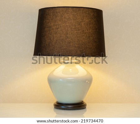 Shinning lamp on bedside table in the bedroom for decoration. - stock photo
