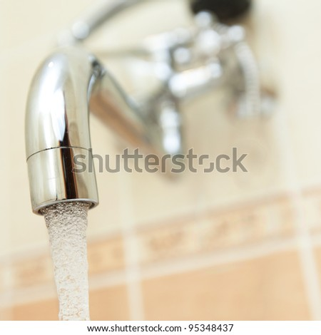 Shinny faucet attached to a wall