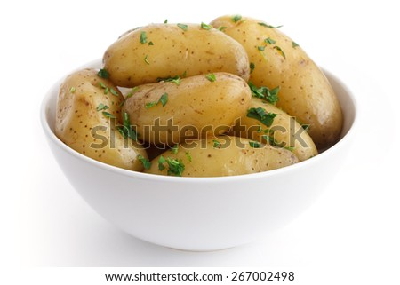 Shiny boiled small potatoes with parsley in bowl.  - stock photo