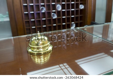 Shiny call bell on hotel reception desk - stock photo