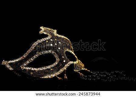 Shiny carnival mask and black pearls over black background