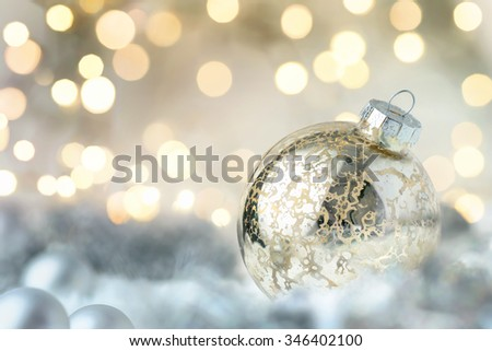 Shiny Christmas bauble closeup with bokeh lights in the background - stock photo