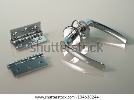 shiny chromed metal door knobs and two hinges close up on the grey background with reflection