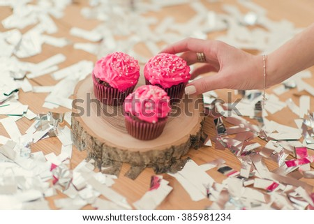 shiny confetti on the table on the wooden deck of pink cupcakes and a female hand - stock photo