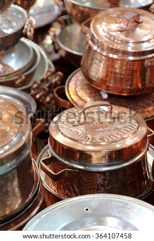 Shiny copper cookware, comprising pots, pans, saucepans. Picture taken in a bazaar / souk in Isfahan, Iran. The external surface is finely chiseled and polished. - stock photo