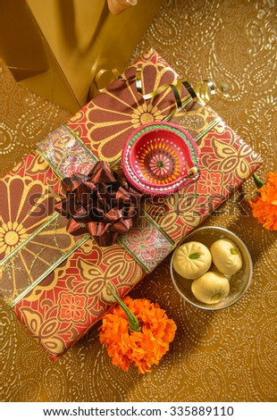 Shiny, decorative and festive gift with Indian sweet and lamp. Indian wedding or festival gifts. - stock photo