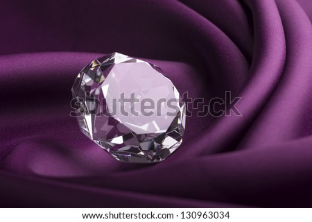 Shiny Expensive Translucent Diamond over Purple Silk Fabric - stock photo