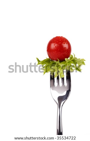 Shiny fork with green salad leaf and red cherry tomato - stock photo