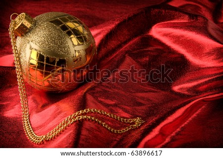 Shiny gold bauble with red background material