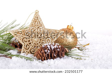 Shiny gold holiday star and pine cone in snow with white background