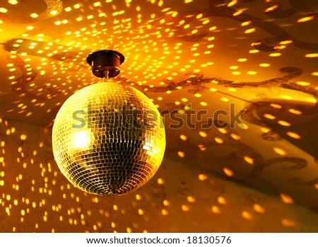 Shiny golden disco ball on nightclub - stock photo