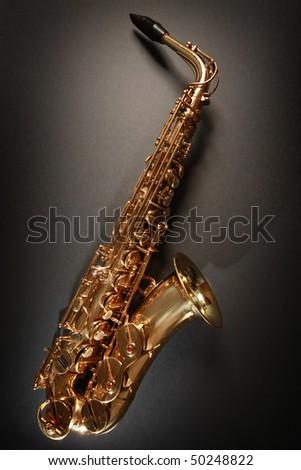 shiny golden saxophone on black background - stock photo