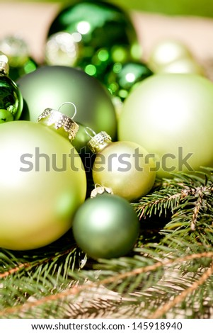 shiny green christmas baubles closeup macro and tree on wooden background - stock photo