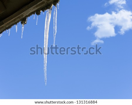 shiny icicles hanging down from a roof against a winter blue sky - stock photo