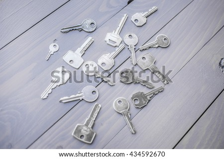 Shiny metal keys on a gray wooden table