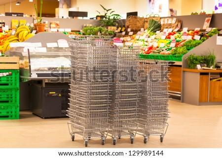 Shiny Metal Shopping Basket Stacks at Supermarket Entrance - stock photo