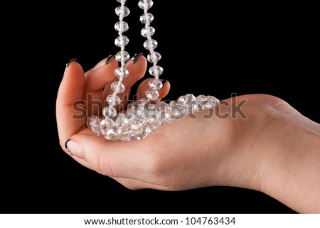 Shiny necklace in a beautiful female hand on a black background.