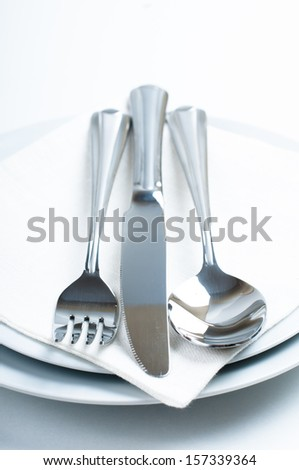 Shiny new cutlery, silverware and a napkin close-up on white background
