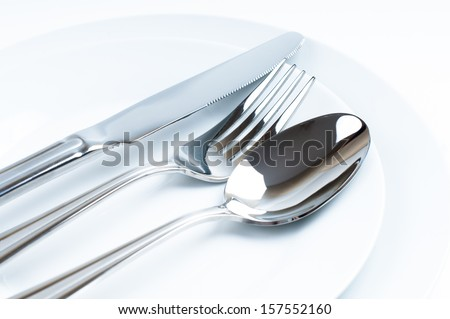 Shiny new cutlery, silverware close-up on white background - stock photo