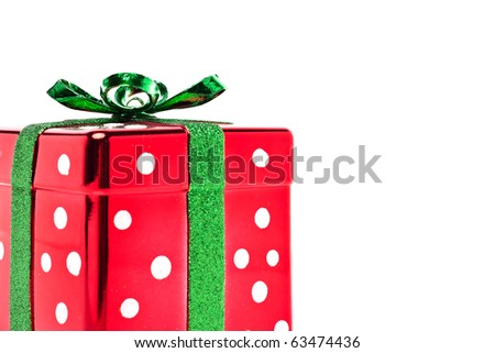 Shiny polka dot red and green Christmas present with lots of copy space - stock photo