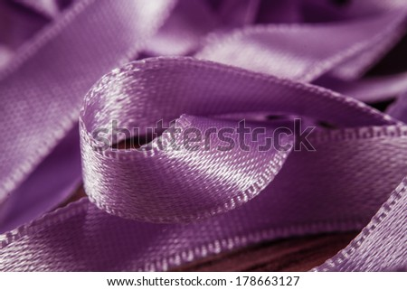 Shiny purple satin ribbons in a messy mess texture background