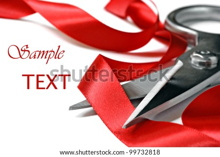 Shiny red satin ribbon curled around stainless steel scissors on white background with copy space.  Macro with extremely shallow dof.   Selective focus limited to ribbon passing through scissors - stock photo