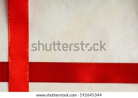 Shiny red satin ribbon stripe on bright cloth background, frame copy space - for luxury, festive events