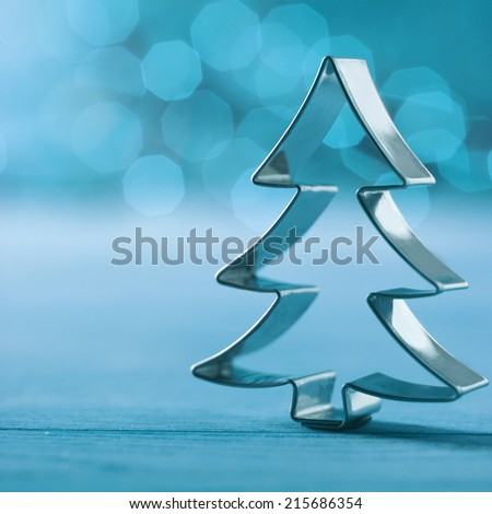 Shiny silver cookie cutter Christmas tree decoration on a wintry cold blue background with a bokeh of twinkling party lights and copyspace , square format - stock photo