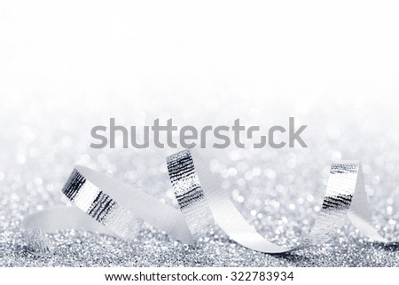 Shiny silver ribbon curls on silver glitters with white copy space - stock photo