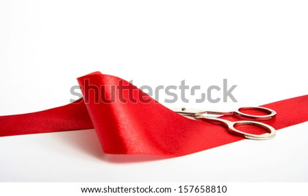 Shiny silver Scissors and red ribbon lying on a white background, the background - stock photo